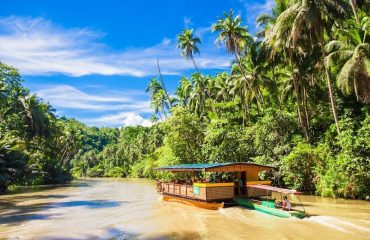 Exotic cruise boat with tourists on a jungle river Loboc, Bohol