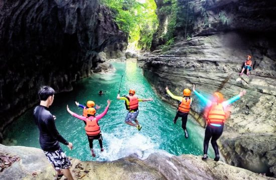 A group of tourist jumping in the natural pool of Kawasan Falls