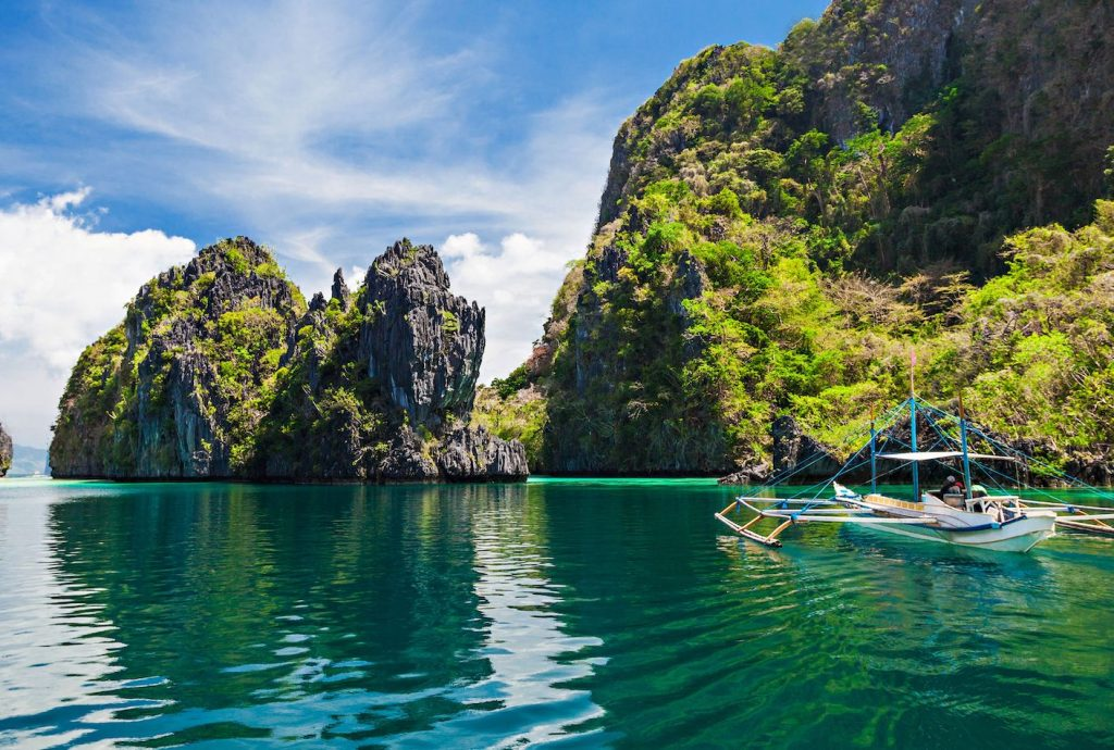 A boat floating on the pristine waters of El Nido's Big Lagoon